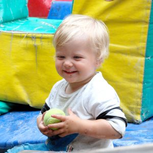 A smiling child holds a tennis ball